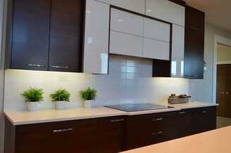 A a kitchen with newly installed modern, dark oak cabinets.